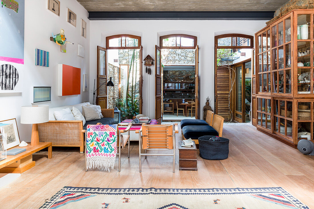 Künstlerisches Wohnzimmer mit drei großen offenen Terrassentüren