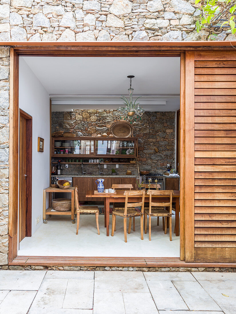 View from terrace through sliding door into rustic dining room