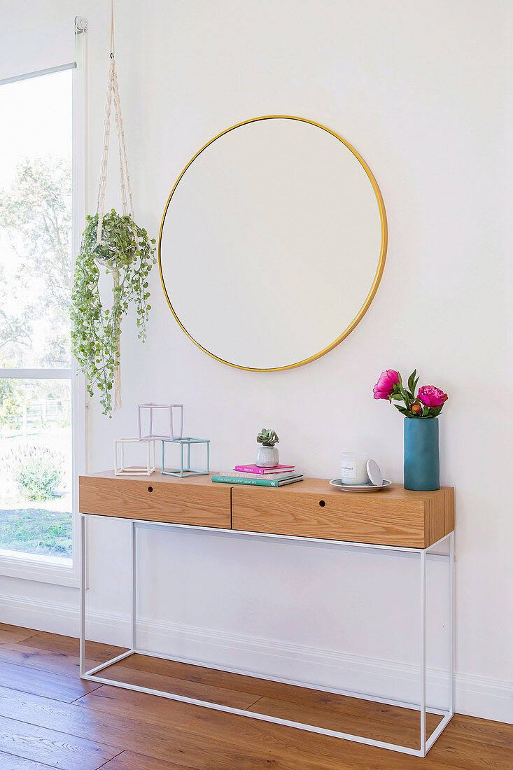 Round mirror over a modern console with a metal frame