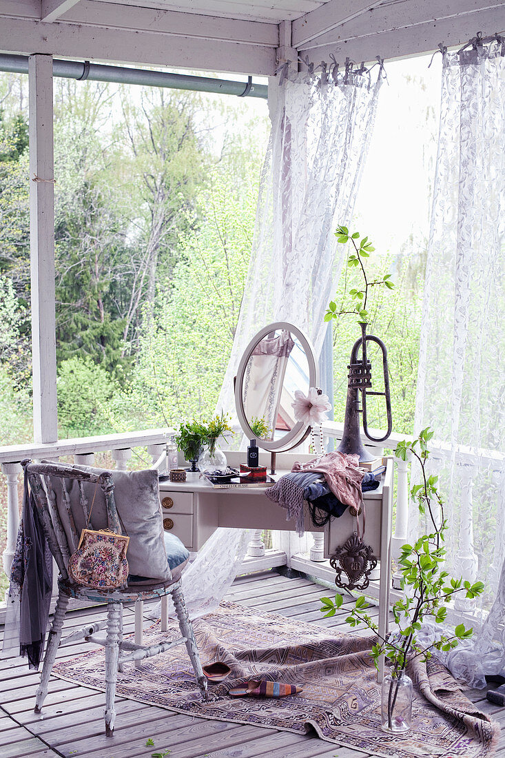 Oval mirror and trumpet used as vase on dressing table and vintage chair on roofed terrace with curtains