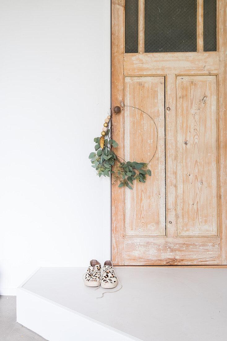Weihnachtlicher Kranz mit Eukalyptusblättern an Holztür
