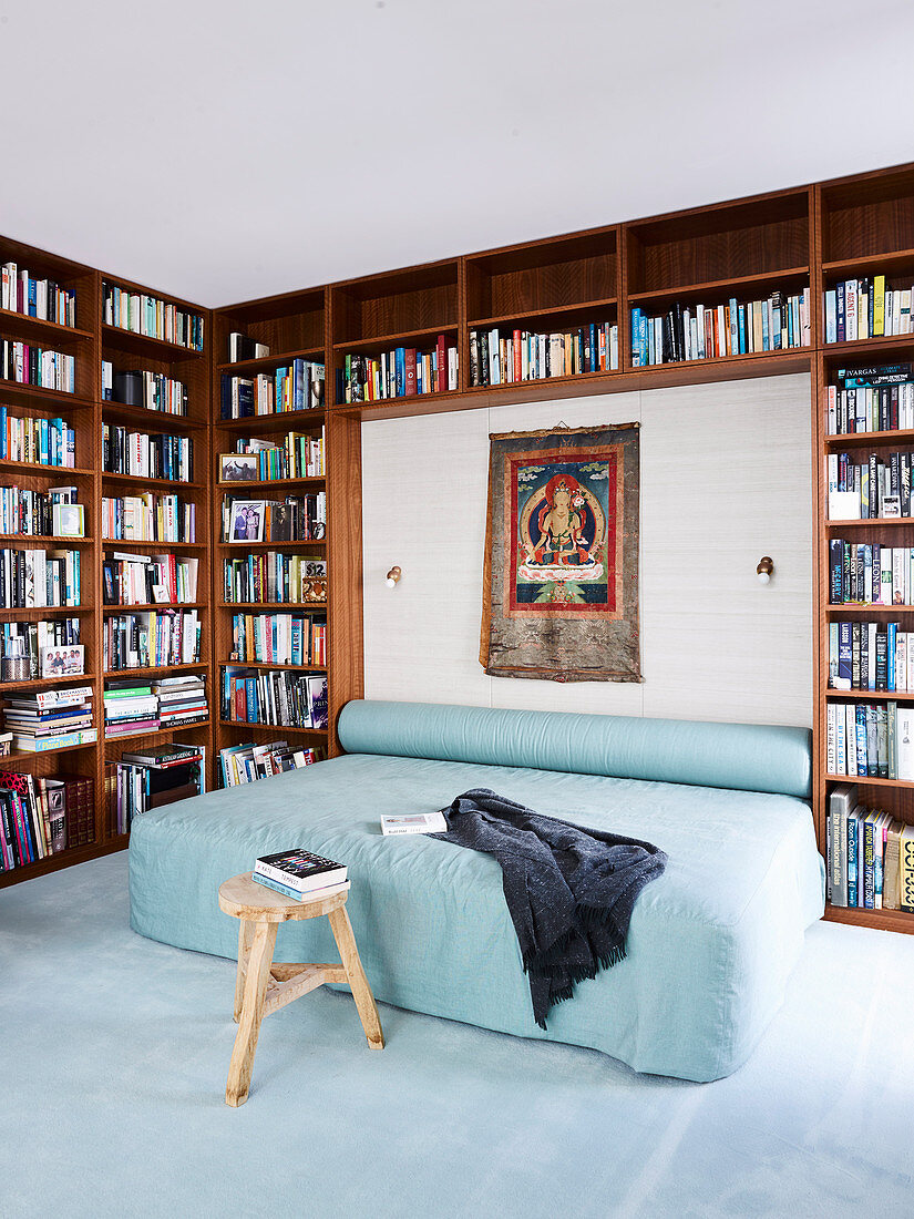Double bed and bolster with light blue cover, framed by the bookcase in the bedroom