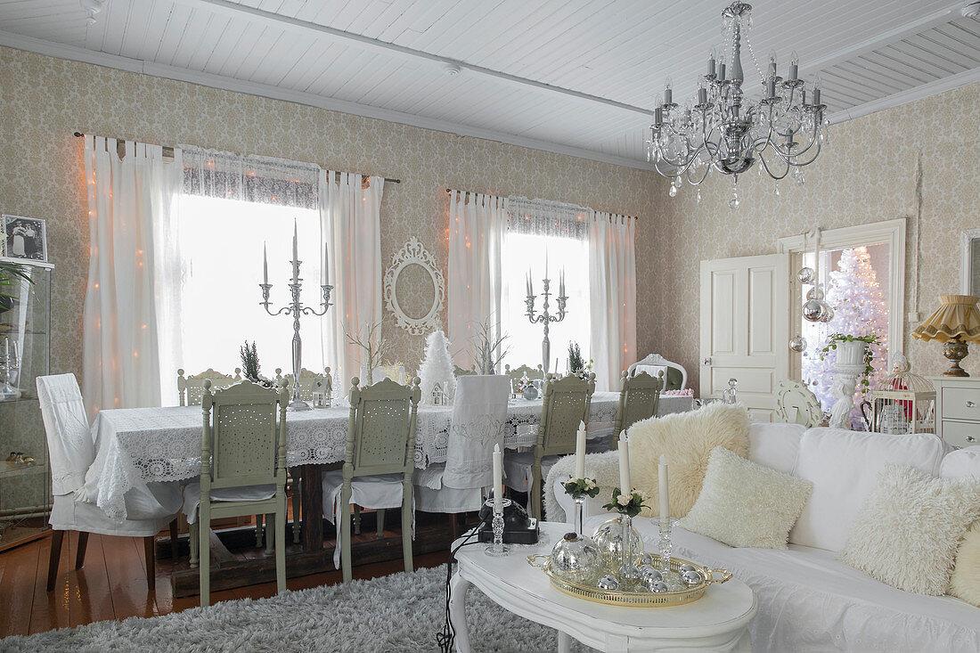 Weißer Couchtisch und Sofa mit Kissen, im Hintergrund Esstafel mit Stühlen
