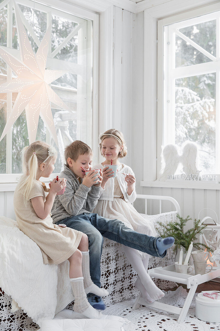Children with drinks in conservatory