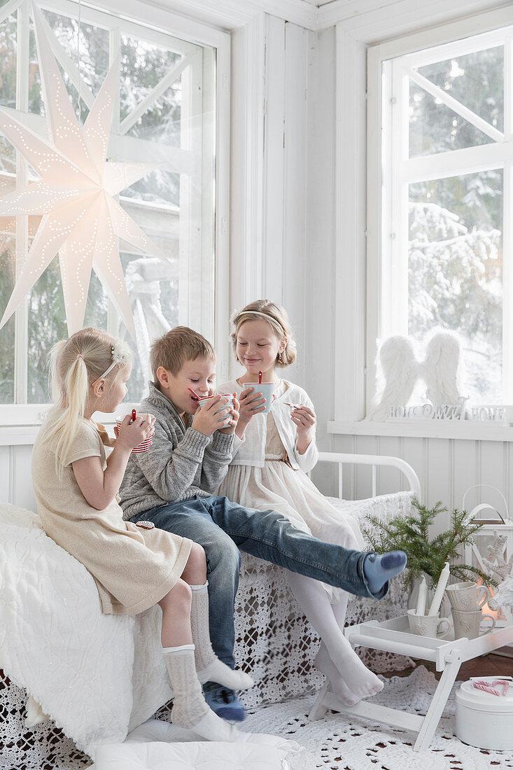 Kinder mit Getränk in weißem Wintergarten