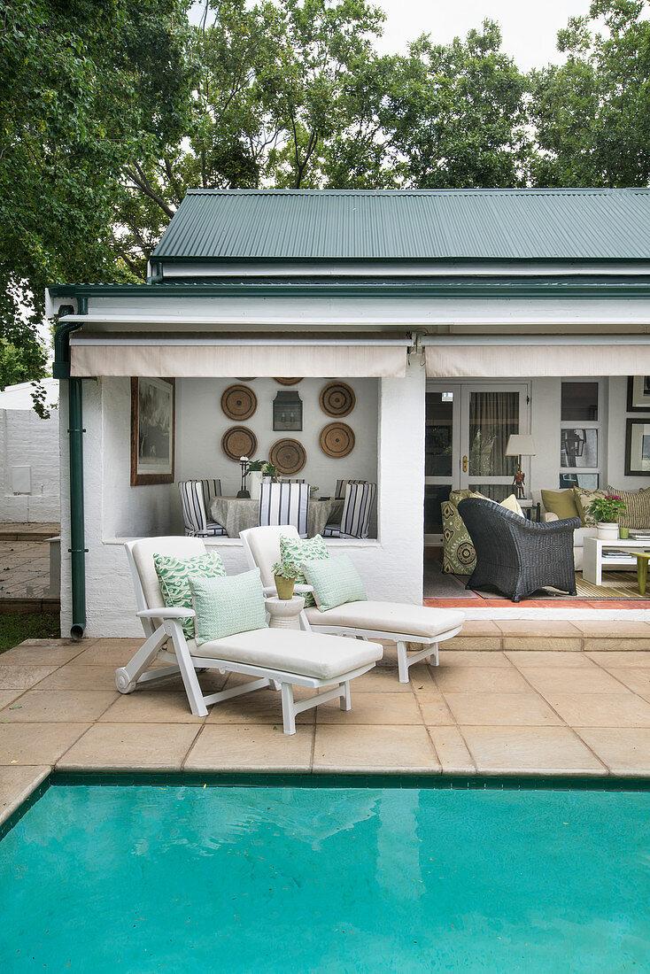 Zwei Liegen auf der Terrasse am Pool vor … – Bild kaufen ...