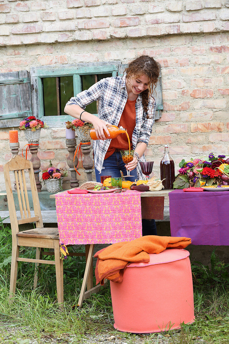 Woman pouring juice at table set for harvest festival in bright colours