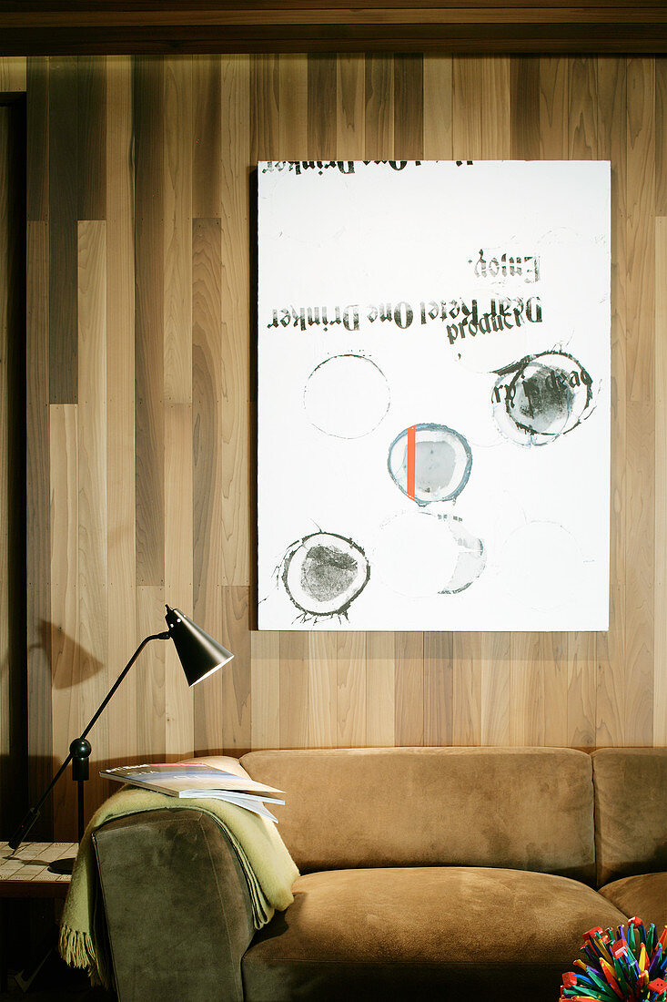 Picture on wood-clad wall over sofa and reading lamp