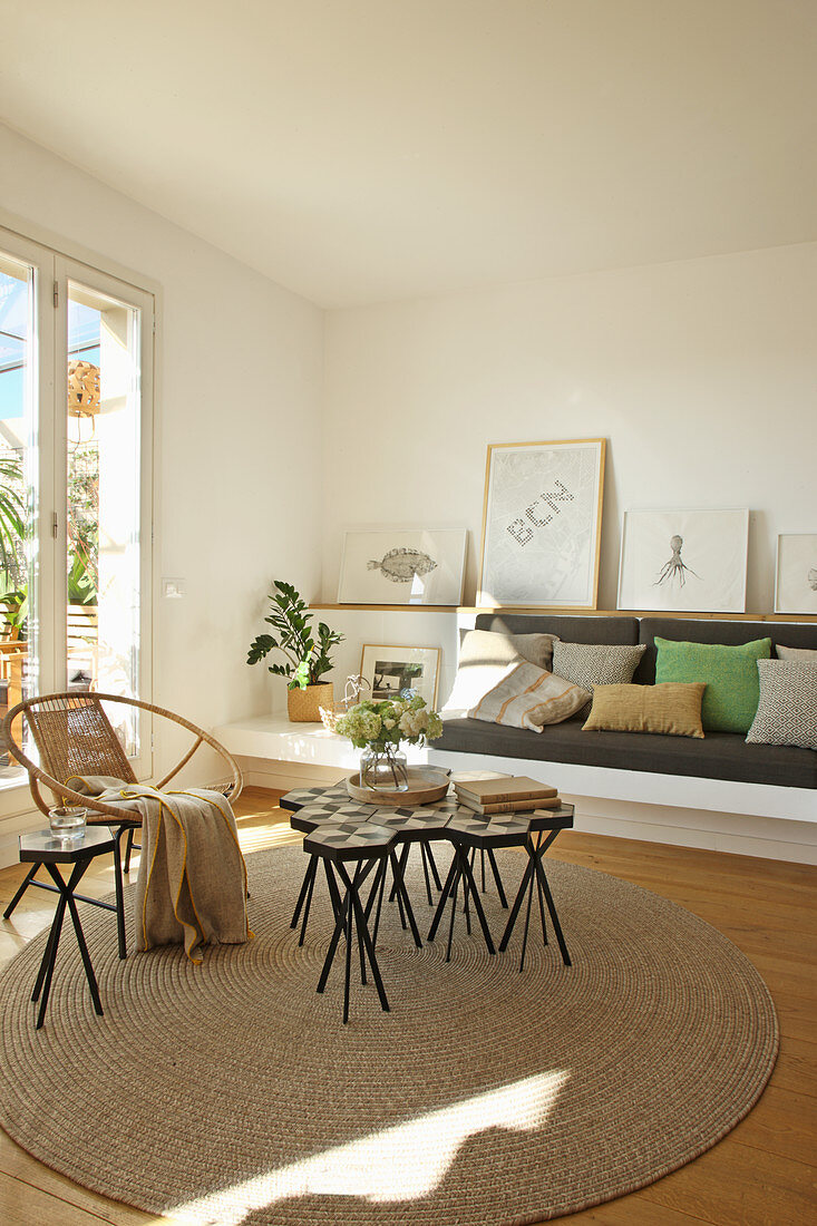 Wicker armchair and set of side tables on round rug