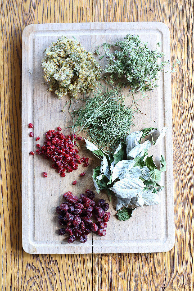 Dried leaves and berries on wooden board for making herbal tea