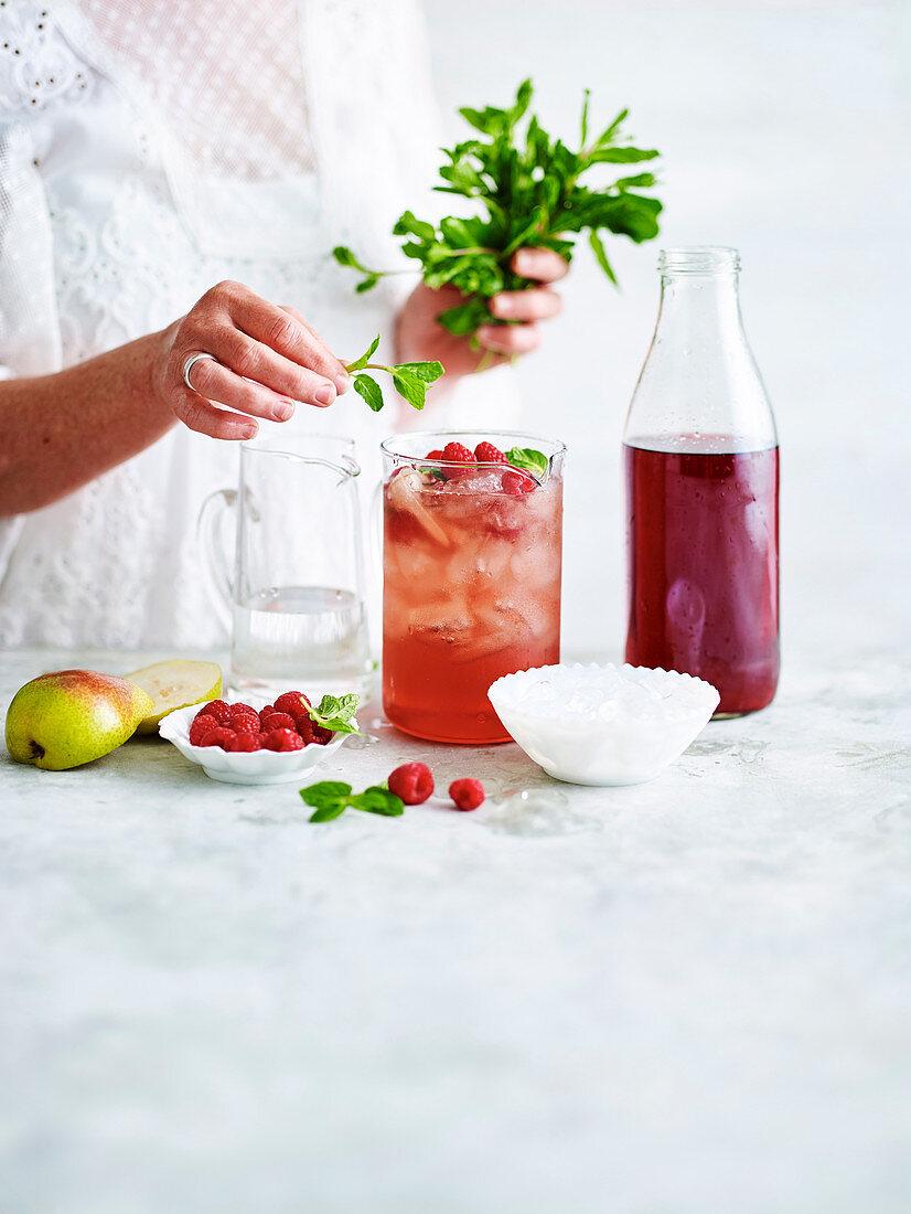 Einen Cranberry-Ingwer-Drink mit Beeren und grünen Blättchen dekorieren