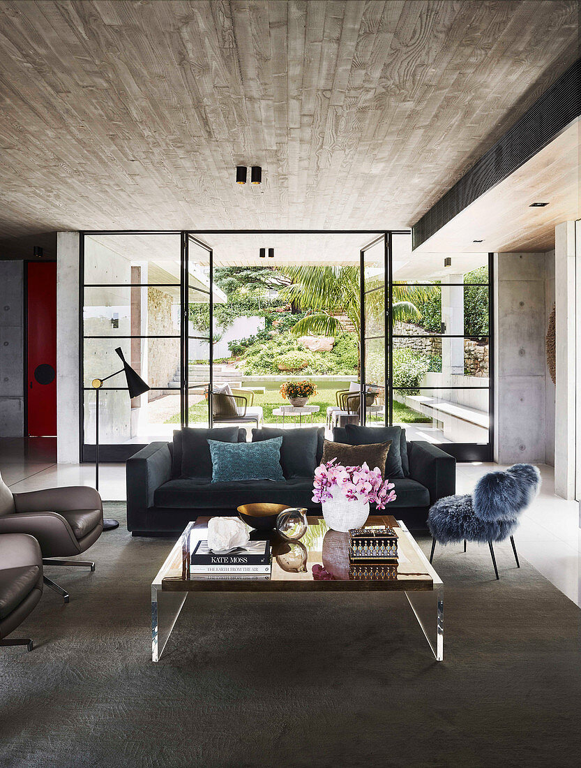 Blue upholstered sofa, fur-look chair and coffee table in open living room, glass patio door in background