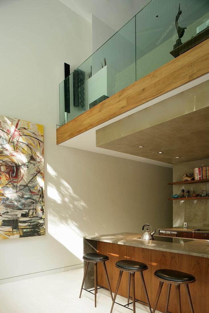 Barhocker an moderner Einbauküche unter der Galerie