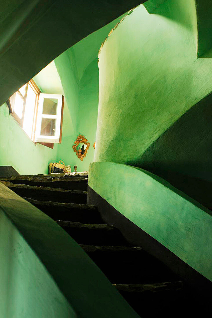 Rustic stairwell with green limewashed walls
