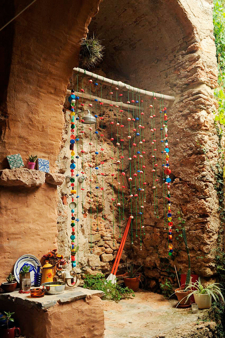 Rustic outdoor shower with bead curtain in stone niche