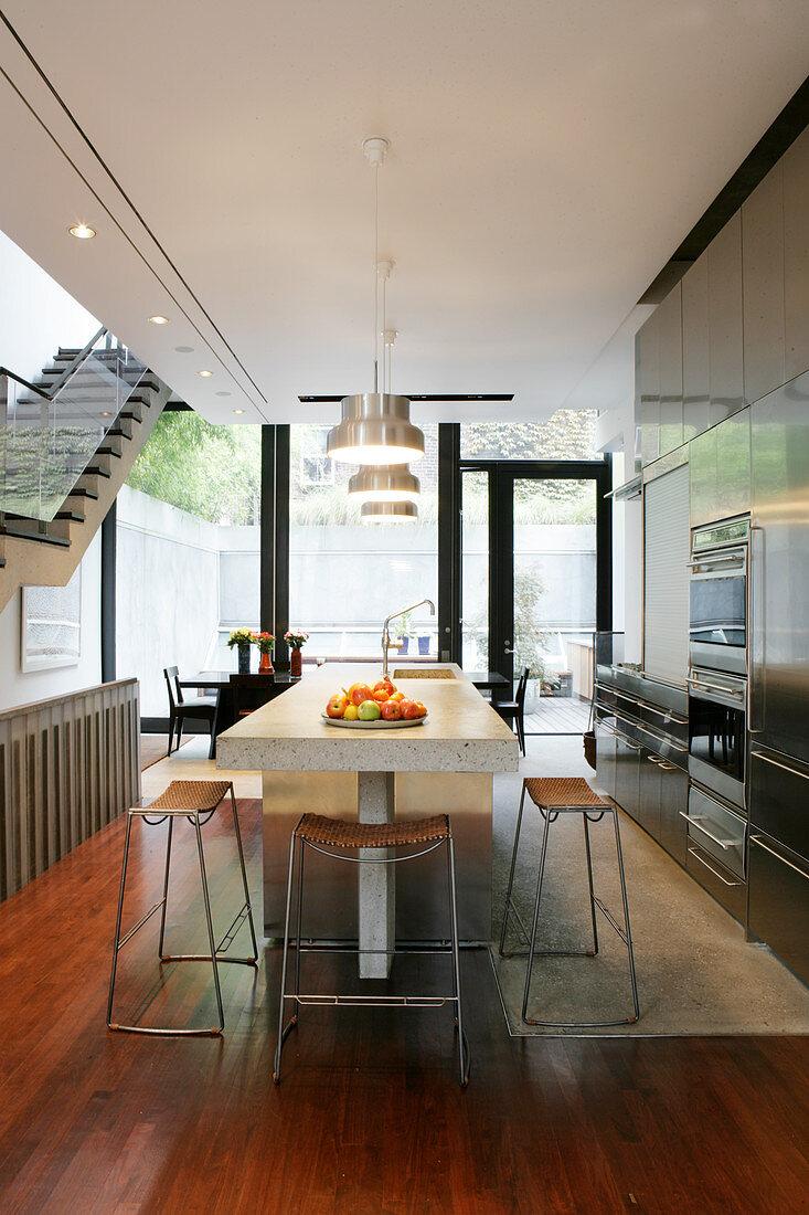 Einbauküche mit Edelstahlfronten und Kücheninsel, im Hintergrund Essbereich vor Terrassentür