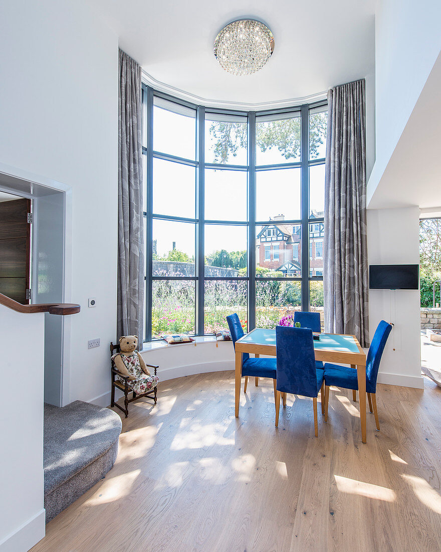 Dining table next to curved window in high-ceilinged room