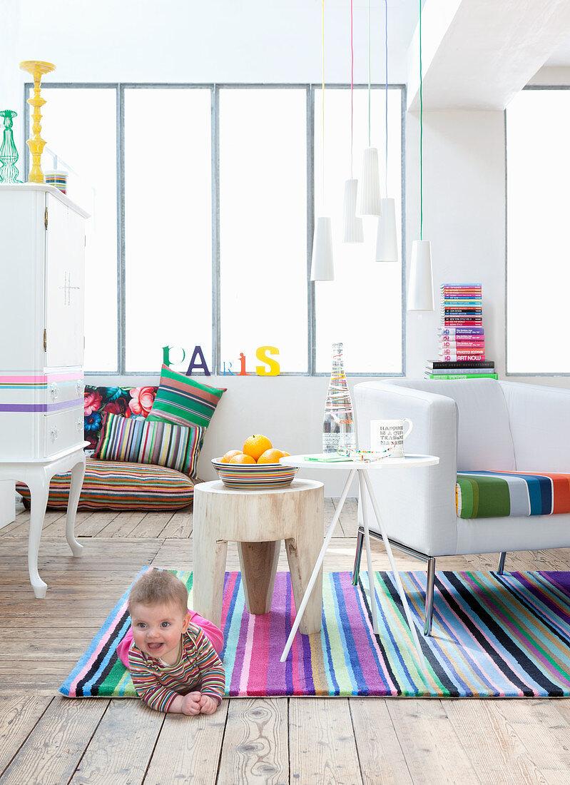 Weißes Wohnzimmer mit bunt gestreiften Accessoires, Kleinkind auf Teppich liegend