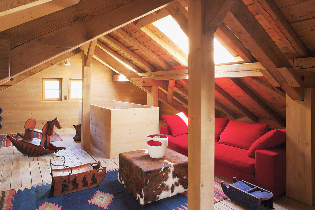 Red sofa, cowhide pouffe and rocking horse in wood-panelled attic room