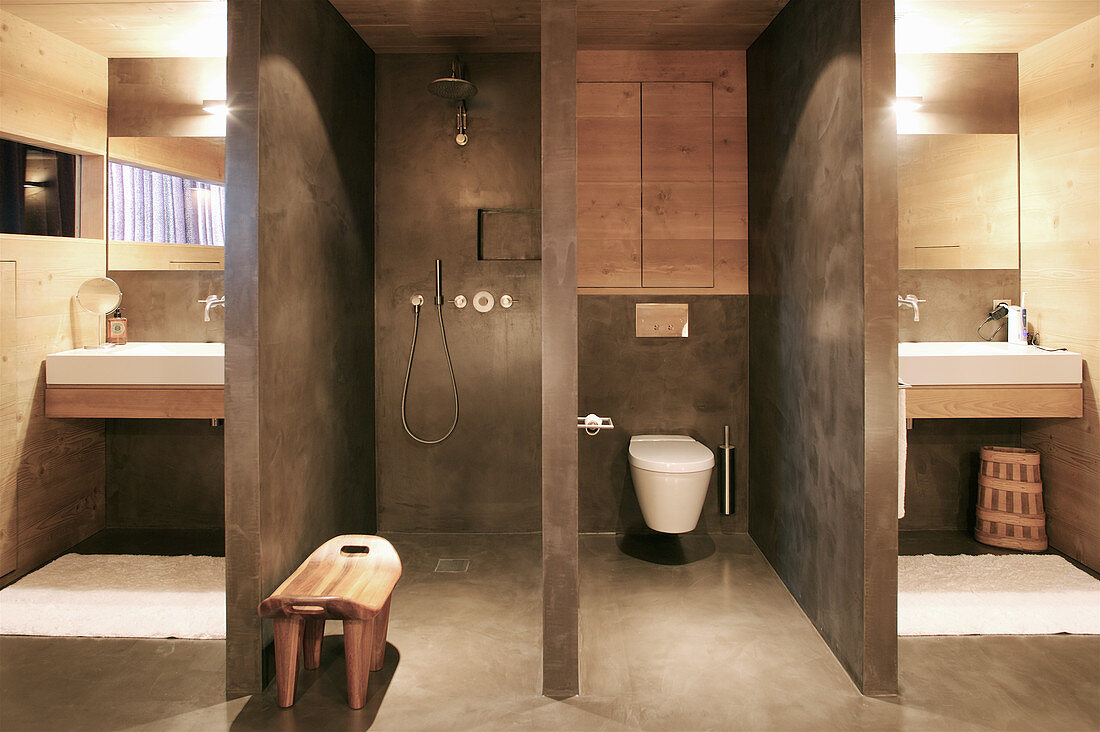 Separate shower and toilet in designer bathroom flanked by sinks on either side