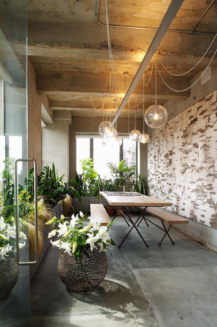 Tisch mit Bänken, darüber Pendelleuchte und Grünpflanzen in der Loggia