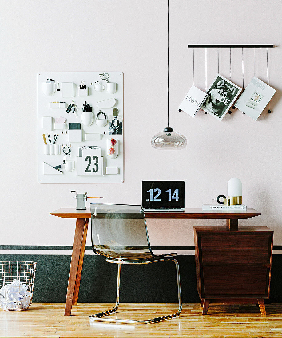 Wooden desk with plastic chair, pendant lamp and wall shelf above to help with organization