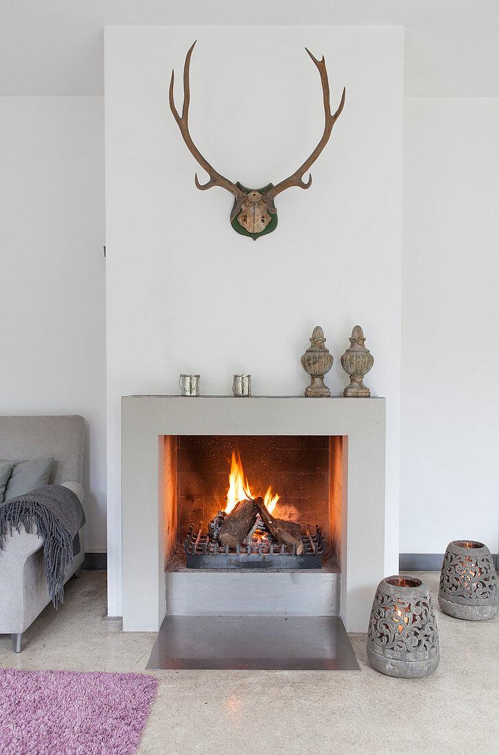 Fire in fireplace below antlers on wall