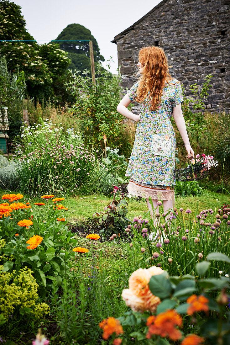 Rothaarige Frau im Blümchenkleid im Garten