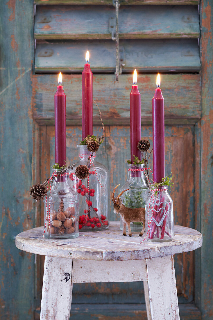 Hand-made festive candlesticks made from bottles filled with natural materials