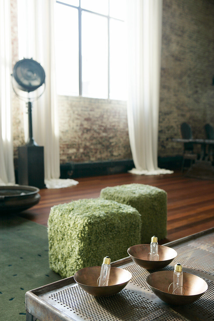 Light bulbs in bowls on coffee table in front of two furry pouffes