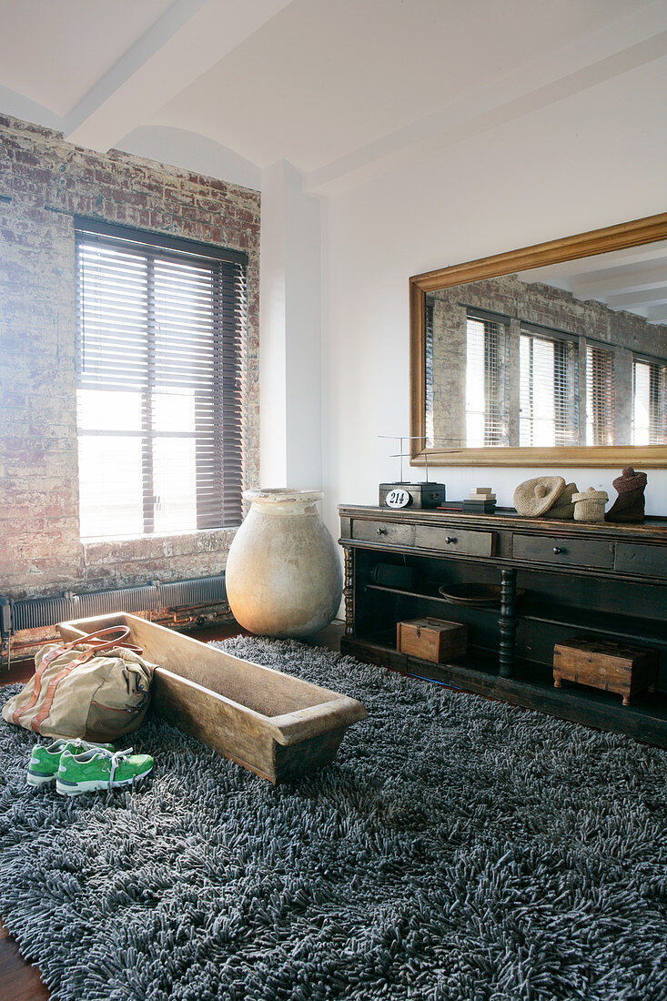 Wooden trough on long-pile rug next to brick wall