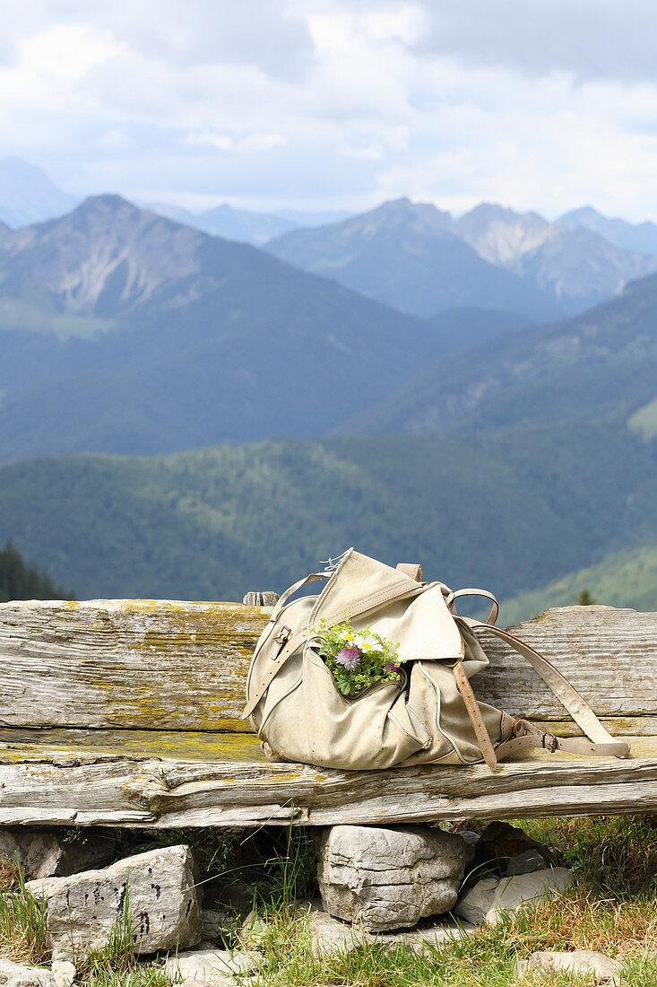Wanderrucksack mit Blumensträusschen auf Holzbank vor Bergpanorama