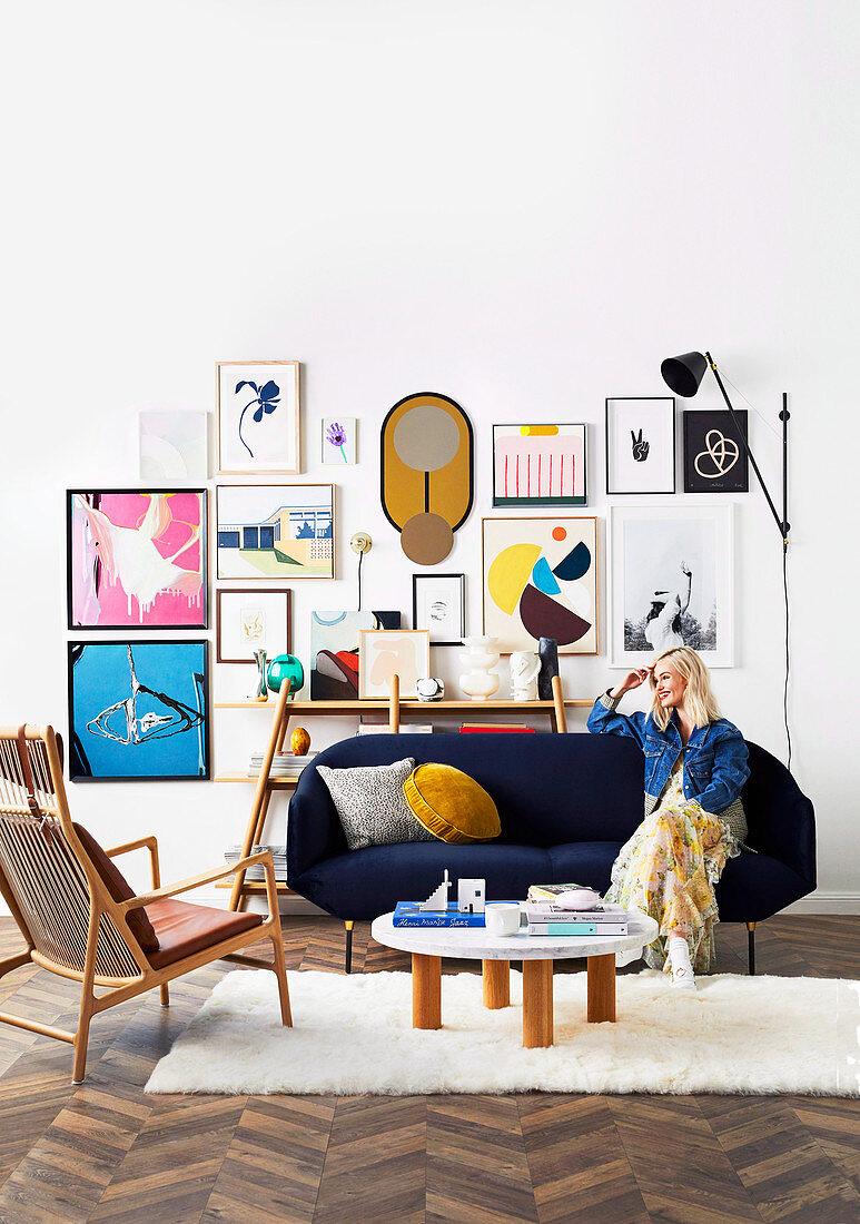 Blond woman sitting on blue sofa, framed artwork on wall