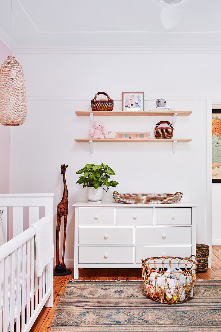 Chest of drawers below shelves in nursery in natural shades