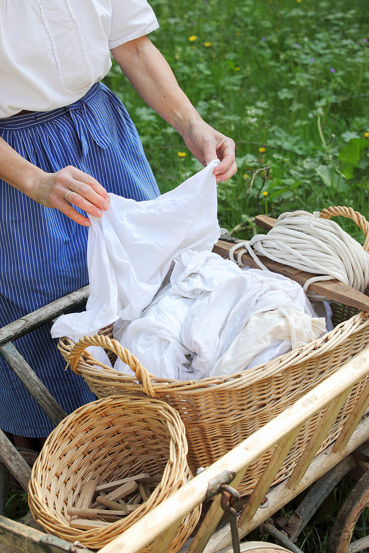 Woman hanging up laundry hand-washed using traditional methods