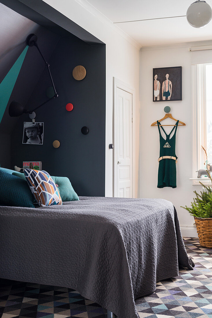 Grey blanket on double bed in bedroom with pale and dark walls