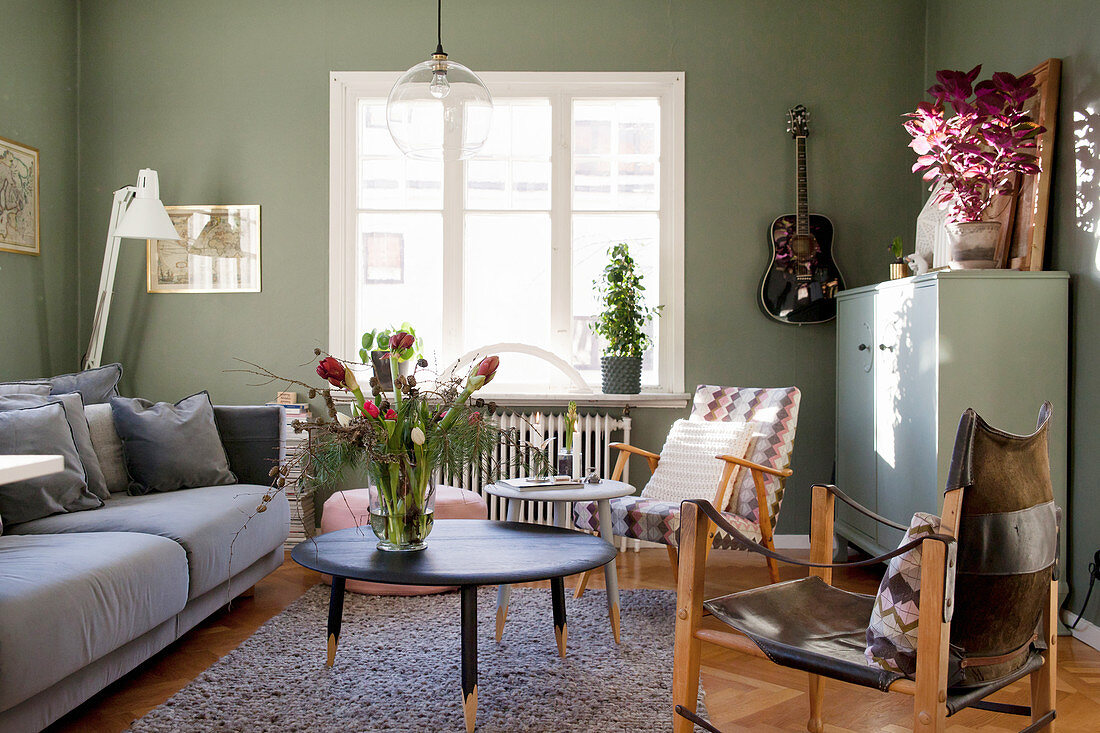 Sofa, coffee table and armchair in living room with green walls