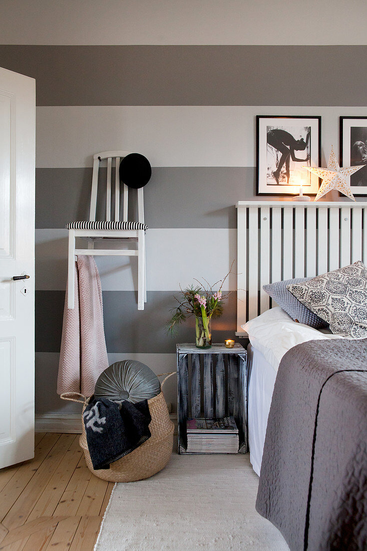 Chair hung on wall as coat rack and crate used as bedside table