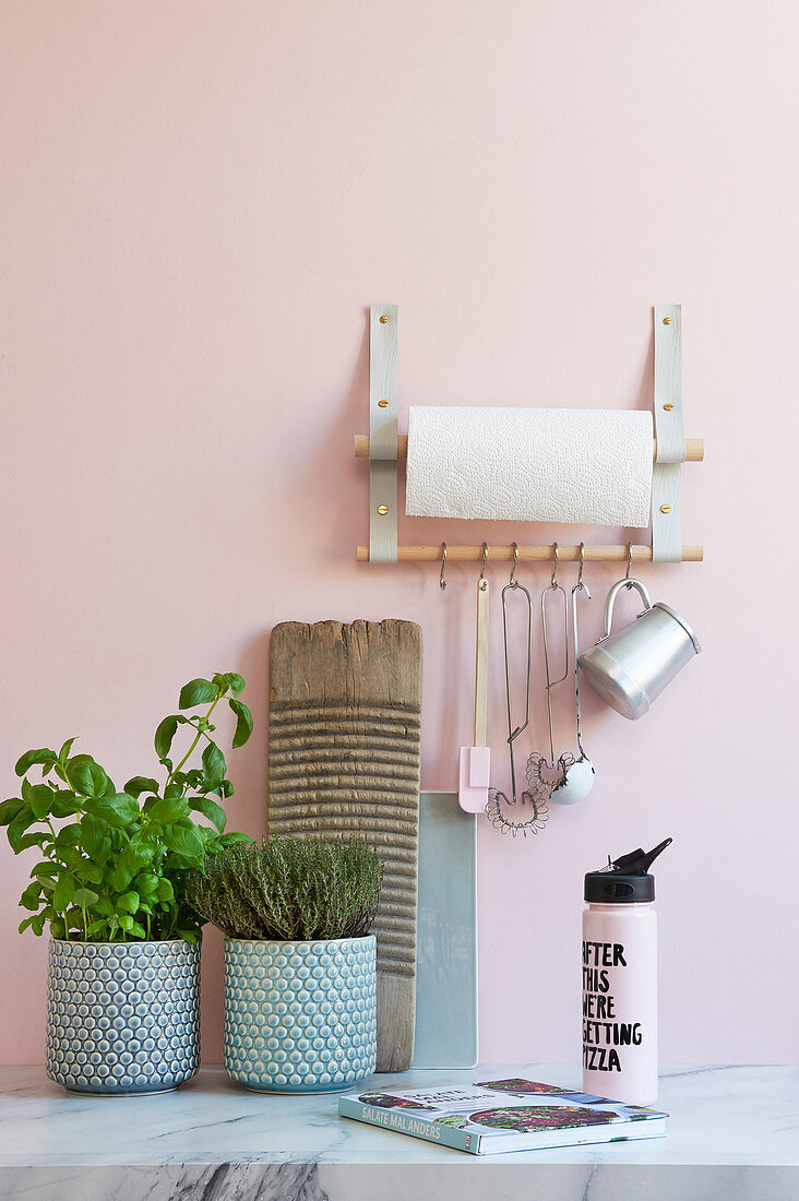 A DIY shelf made of leather straps for kitchen utensils