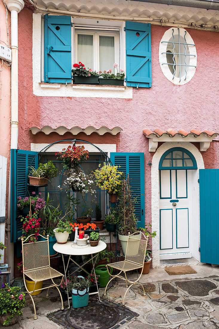 Romantic seating area outside pink house with blue shutters
