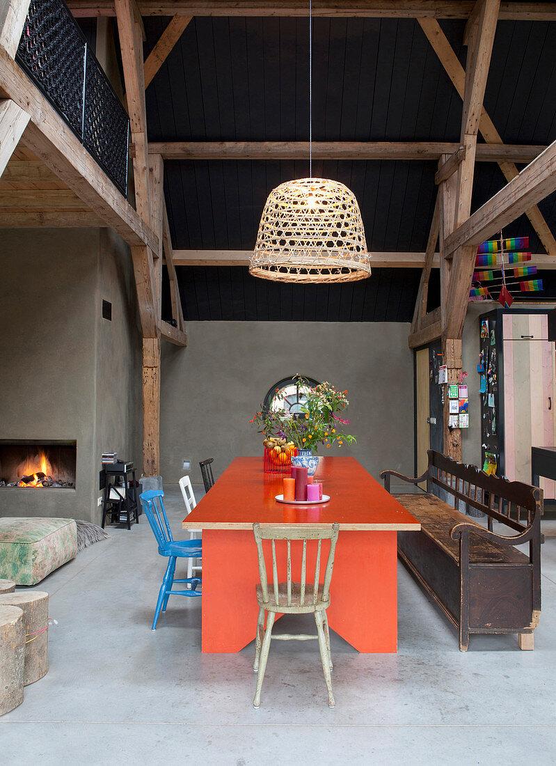 Moderner roter Tisch im offenen Wohnraum eines Bauernhauses