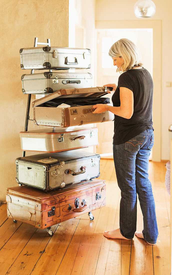 Blonde woman in front of handmade chest of drawers made from vintage suitcases and metal frame