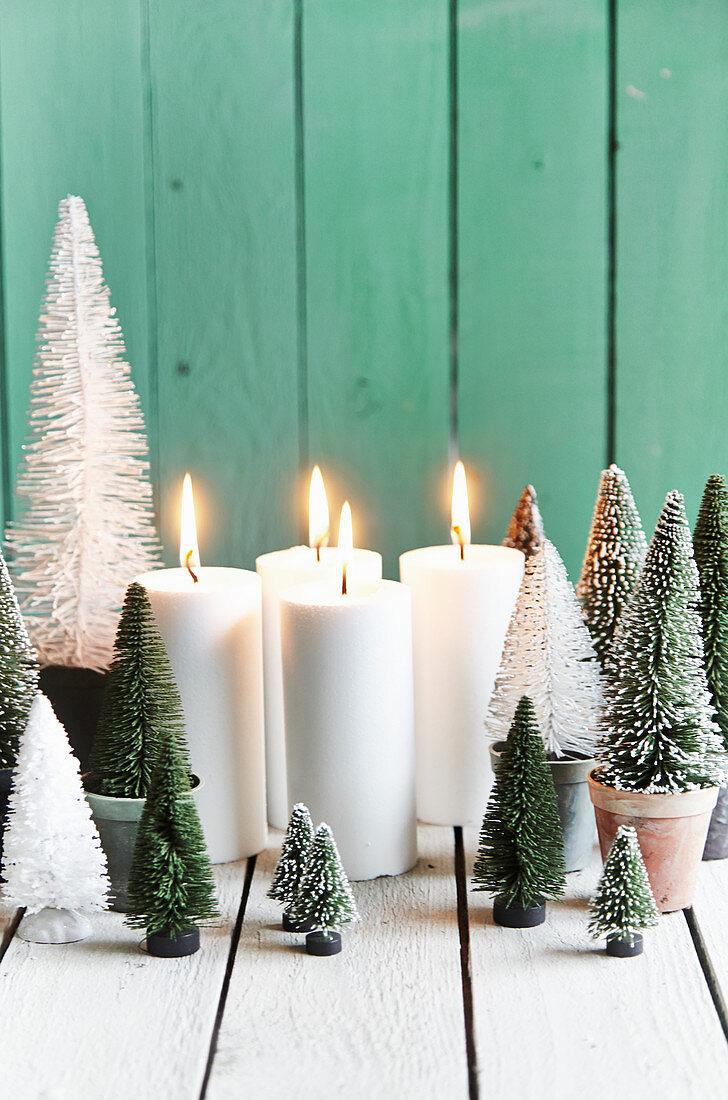 Adventsdeko: Miniatur-Tannenbäume aus Kunststoff und vier brennende Kerzen