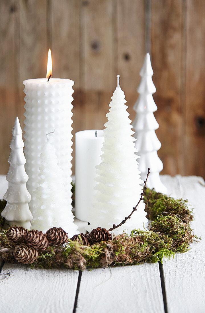 DIY-Kranz aus Moos und Lärchenzweigen mit weißen Weihnachtskerzen