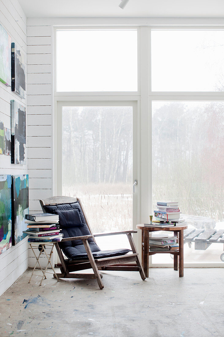 Vintage armchair and stacked books on side tables next to terrace doors and paintings on white wooden wall