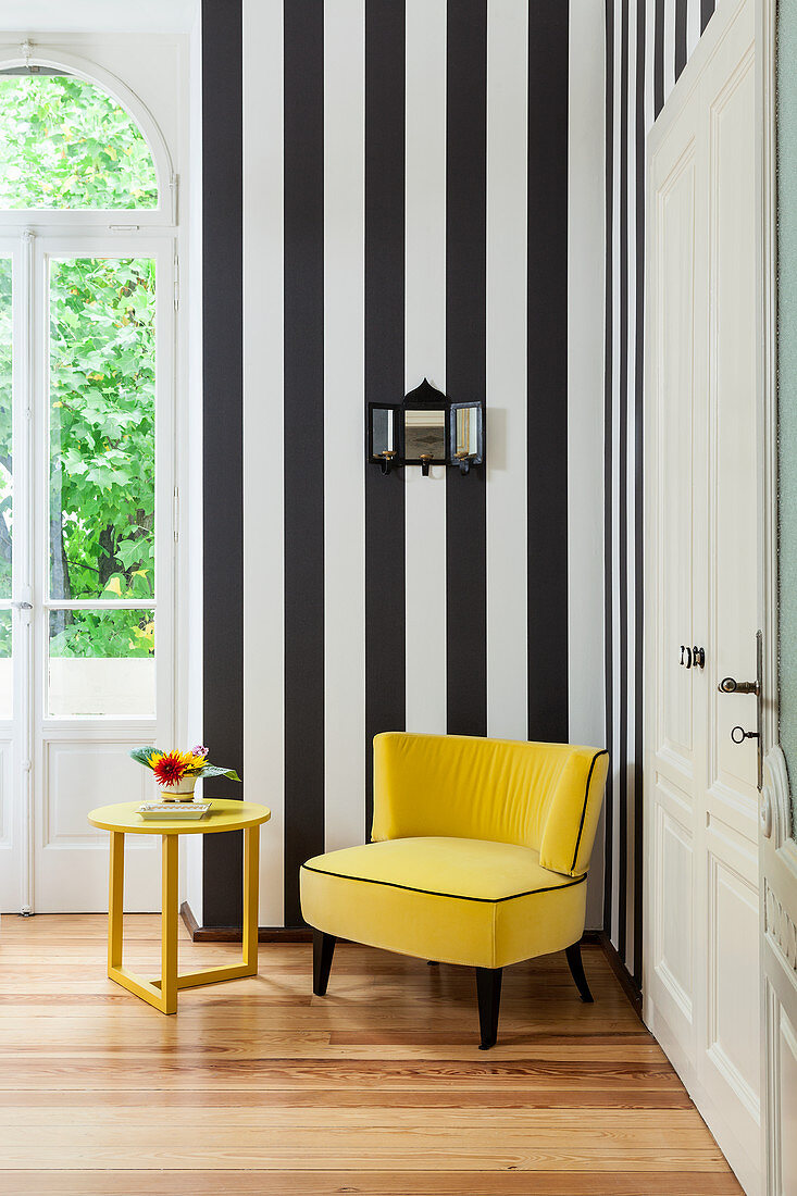 Yellow velvet armchair and side table against black-and-white striped wall