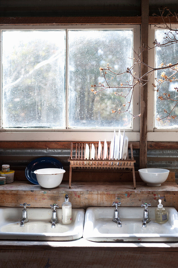 Twin sinks and draining rack below window