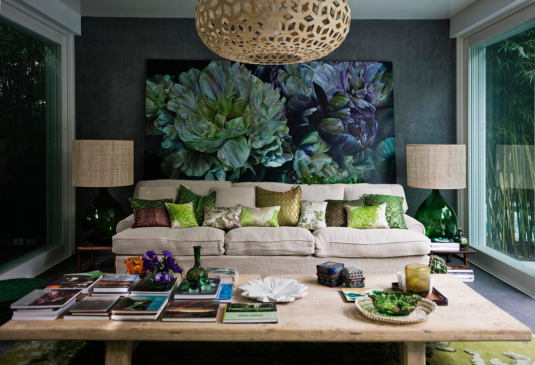View of books on wooden table and sofa with scatter cushions below large painting on wall