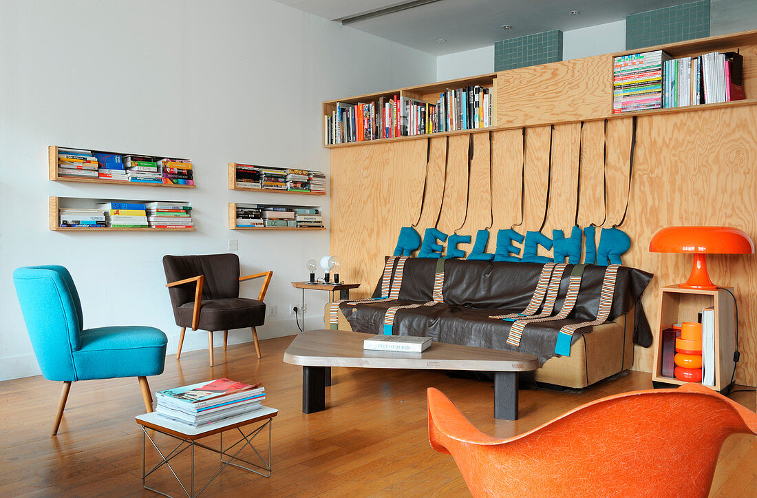 Thin leather throw on sofa against chipboard wall and various retro chairs in loft apartment