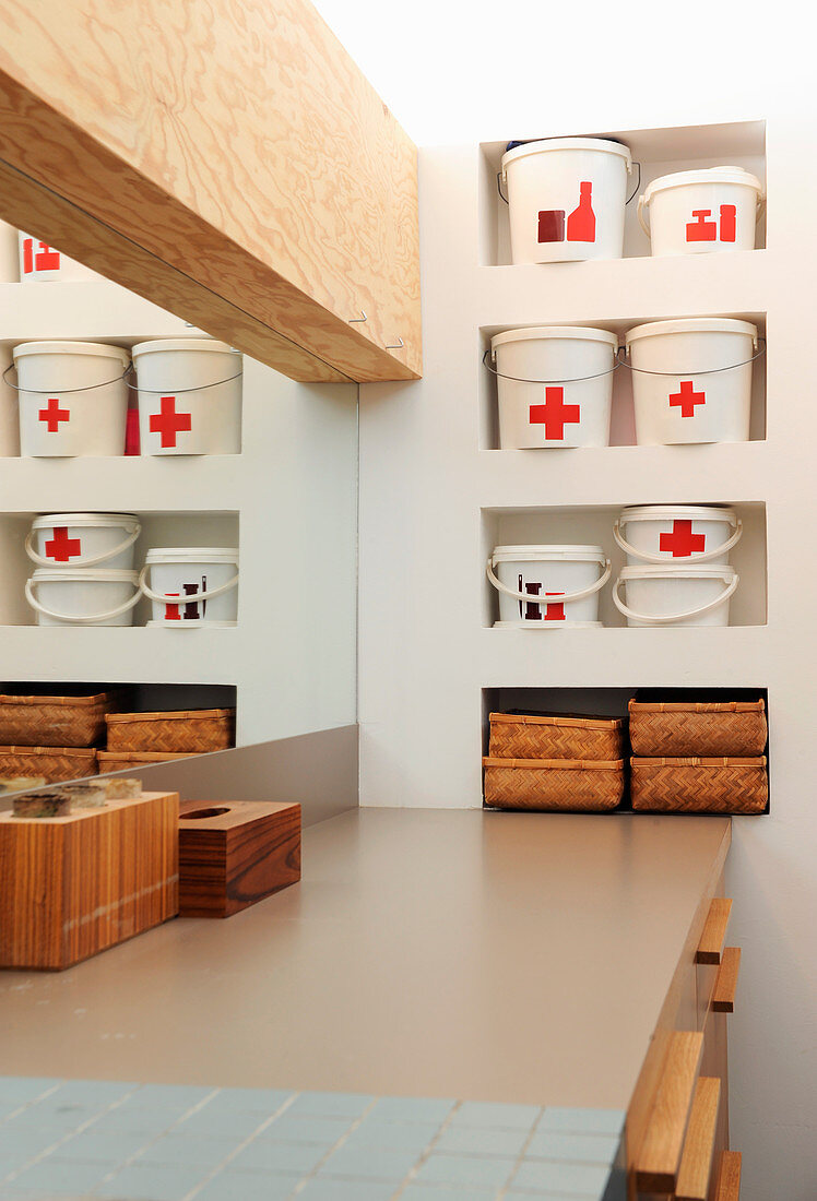 Recycled plastic buckets in niches in bathroom wall